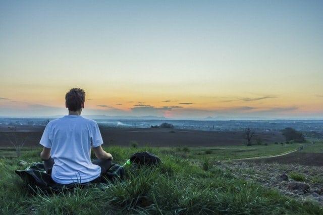Man meditating on a mountain